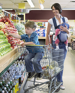 Woman and two small children shopping in produce section of grocery store.