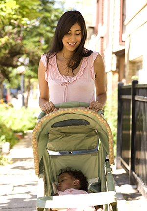 Woman walking baby in stroller.