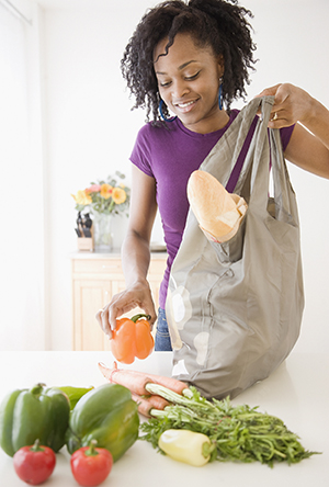 Woman taking fresh vegetables out of shopping bag.