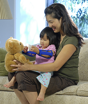 Toddler with arm restraints playing with teddy bear while sitting in woman's lap.