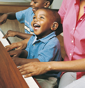 Toddler with hearing aid in ear sitting on woman's lap, playing piano.