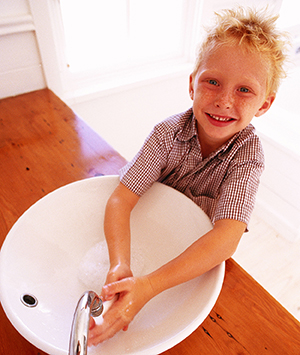 Boy washing hands with soap in sink.