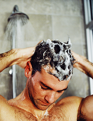 Man shampooing hair in shower.
