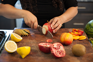 Woman slicing fruit on cutting board.