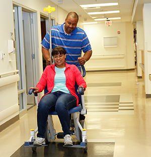 Man pushing woman in wheelchair in hospital hallway.