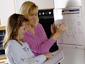 Woman and girl writing on calendar on refrigerator.