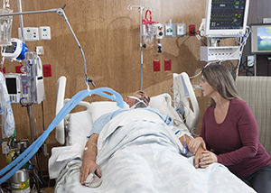 Woman sititng next to bed of intubated man in intensive care unit.