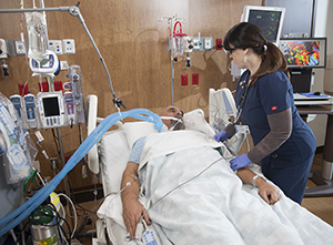 Healthcare provider caring for intubated patient in intensive care unit.