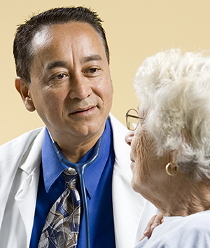 Healthcare provider talking to elderly woman.