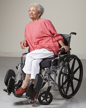 Woman in wheelchair leaning to side to take pressure off one leg.