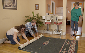 Young couple rolling up a rug for an older woman.