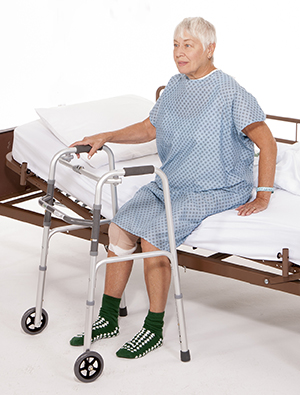 Woman sitting on edge of hospital bed with walker.