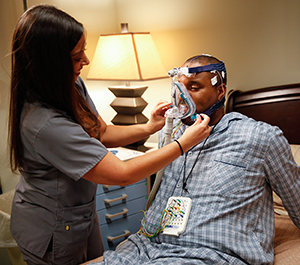 Technician preparing man for sleep study.