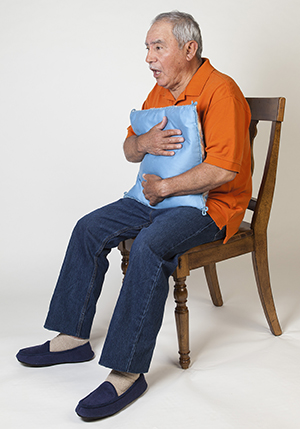 Man holding pillow to chest, coughing.