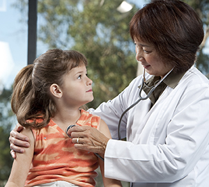 Healthcare provider listening to girl's chest with stethoscope.