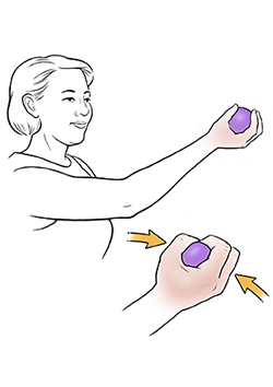 Woman doing ball squeeze exercise.