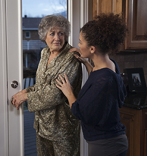 Woman preventing senior woman from going out kitchen door.