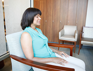 Woman relaxing in chair with eyes closed.
