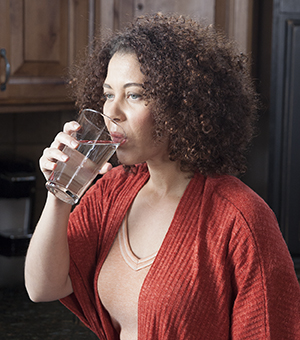 Woman drinking glass of water in kitchen.