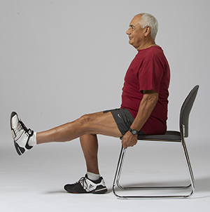 Man sitting in chair doing leg lift exercise.