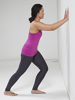 Woman doing standing calf stretch exercise.