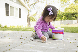 Female toddler playing with chalk on paving slabs.