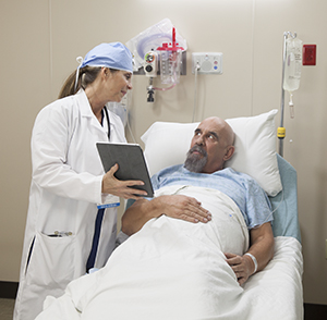 Healthcare provider talking to man in pre-op hospital room.
