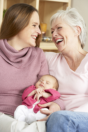 New mother and grandmother holding newborn baby daughter.