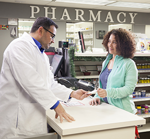 Pharmacist talking to woman at pharmacy counter.