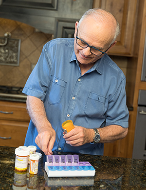Man filling pill organizer with medications.