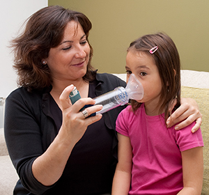 Woman helping girl use mask inhaler with spacer.