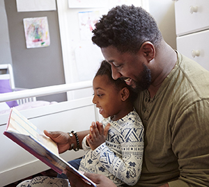 Man reading book to child at bedtime.