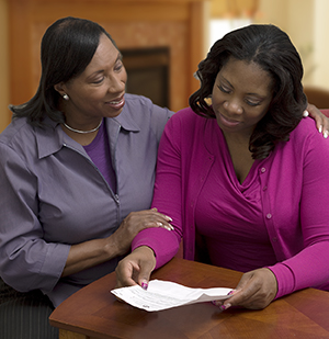 Two women reading paperwork together.