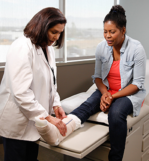 Healthcare provider examining cast on woman's leg.