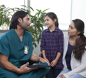 Healthcare provider talking with woman and girl.