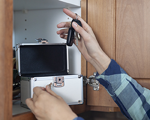 Woman putting keys in locking box in kitchen cabinet.