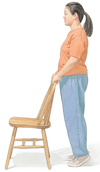 Woman standing on tiptoes and holding on to chair for support.