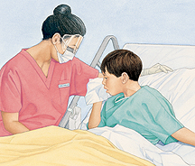 Health care provider wearing face mask, face shield, and gloves standing next to boy in hospital bed. He is coughing into tissue.