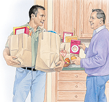 Man bringing grocery bags into kitchen while another man puts groceries away.
